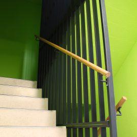 Een lamellen traphek en houten leuning geproduceerd door Straatman Balustraden en Trappen